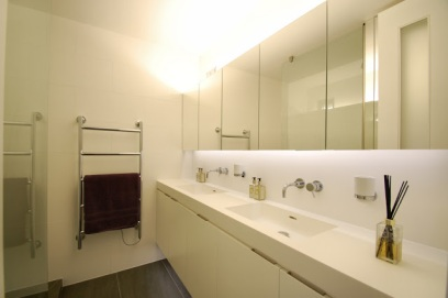 The bathroom has been adapted to create a large walk-in shower. A bespoke corian vanity top has two inset sinks with lots of useful storage in the cupboards below and the wall to wall mirrored cabinets above.