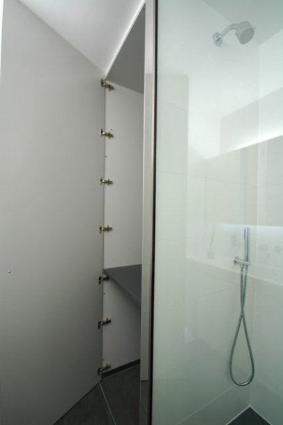Space for a washing machine is provided in the tall mirrored airing cupboard behind the walk-in shower.